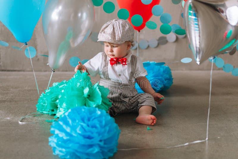 Bebé feliz que celebra el primer cumpleaños Fiesta de cumpleaños de los niños adornada con los globos y la bandera colorida imagen de archivo libre de regalías
