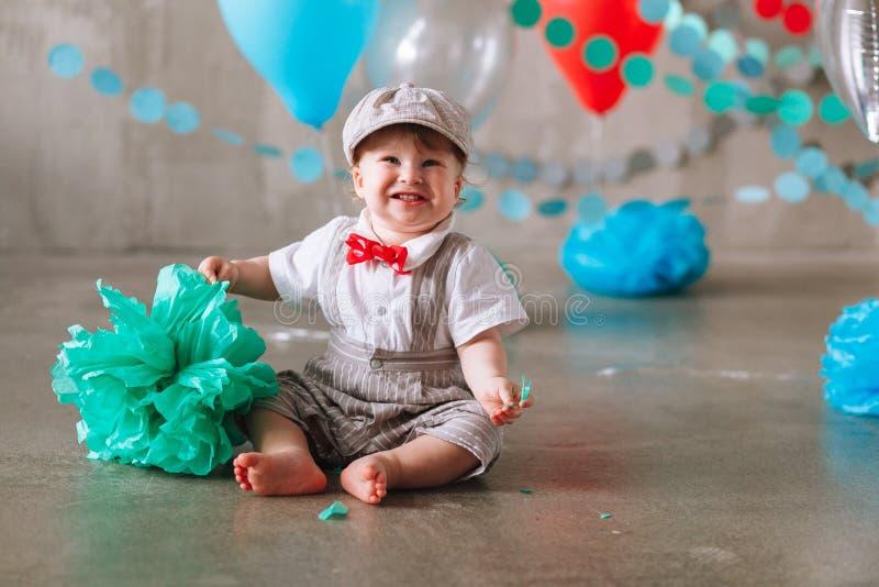 Bebé feliz que celebra el primer cumpleaños Fiesta de cumpleaños de los niños adornada con los globos y la bandera colorida foto de archivo libre de regalías
