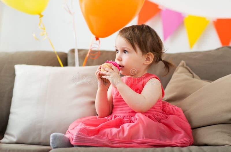 Bebé feliz que come la magdalena en fiesta de cumpleaños imagen de archivo