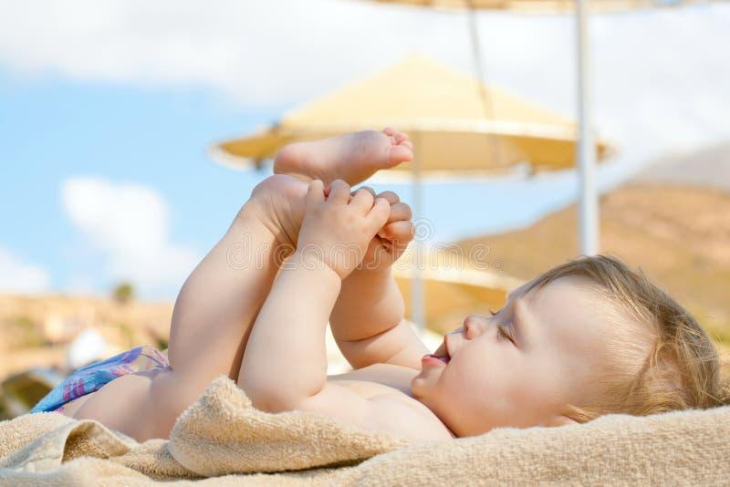 Bebé feliz que descansa sobre la playa sunbed fotos de archivo libres de regalías