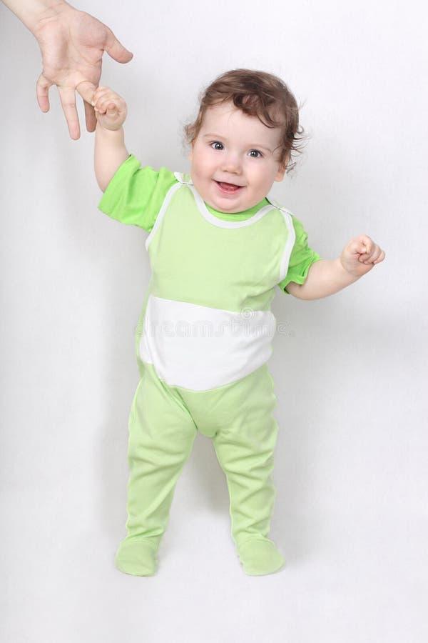 Bebé feliz que hace los primeros pasos fotografía de archivo