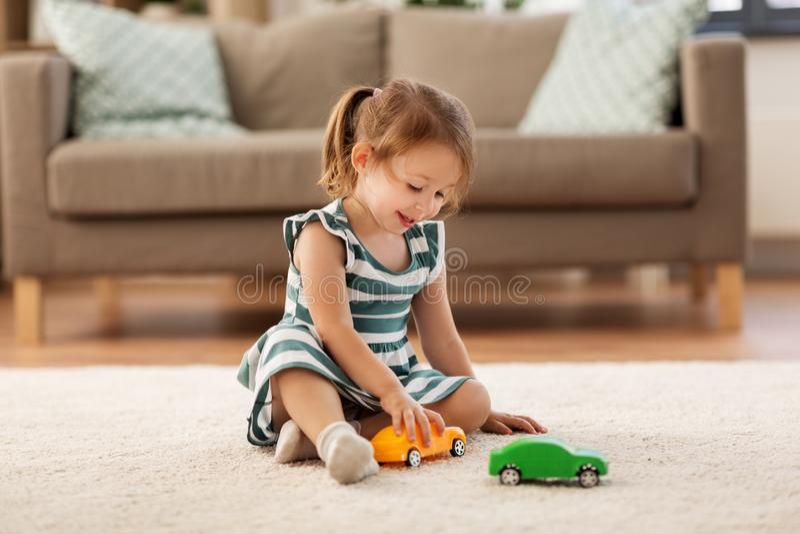 Bebé feliz que juega con el coche del juguete en casa fotos de archivo