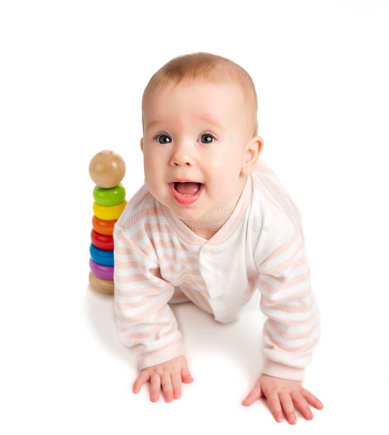 Bebé feliz que juega con una pirámide del juguete aislada foto de archivo