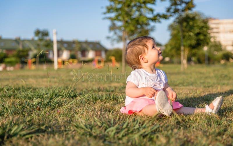 Bebé feliz que juega sentarse en un parque de la hierba fotografía de archivo