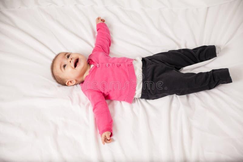 Bebé feliz que miente en una cama imagenes de archivo