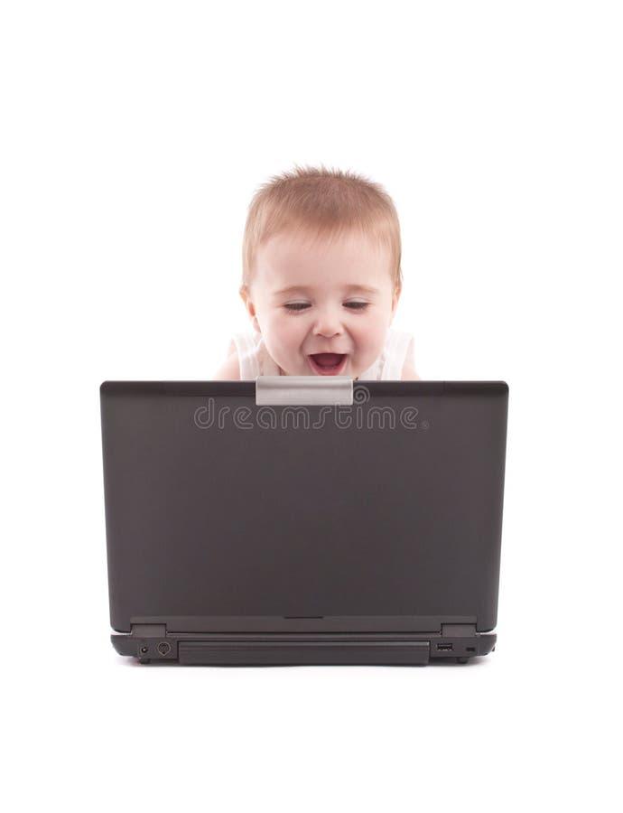 Bebé feliz que mira la computadora portátil fotografía de archivo