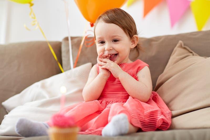 Bebé feliz que mira la magdalena del cumpleaños imagen de archivo libre de regalías