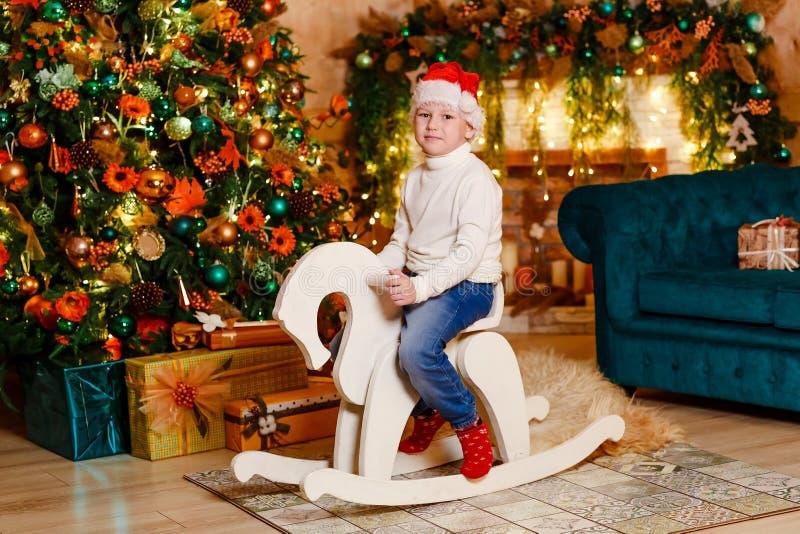 Bebé feliz que monta un caballo mecedora de madera del juguete en un cuarto adornado de la Navidad fotos de archivo