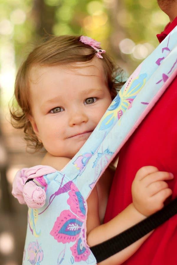 Bebé feliz que se sienta en una honda que lleva. imagenes de archivo