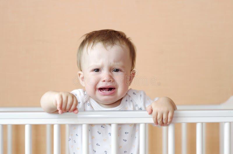 Bebé gritador en la cama blanca imagenes de archivo
