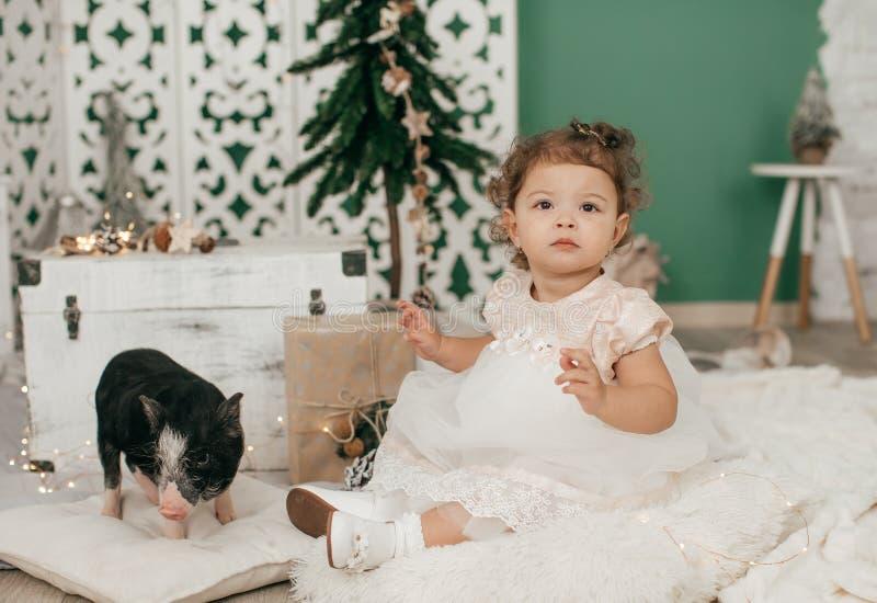 Bebé hermoso cerca de un árbol de navidad con los regalos con fotos de archivo