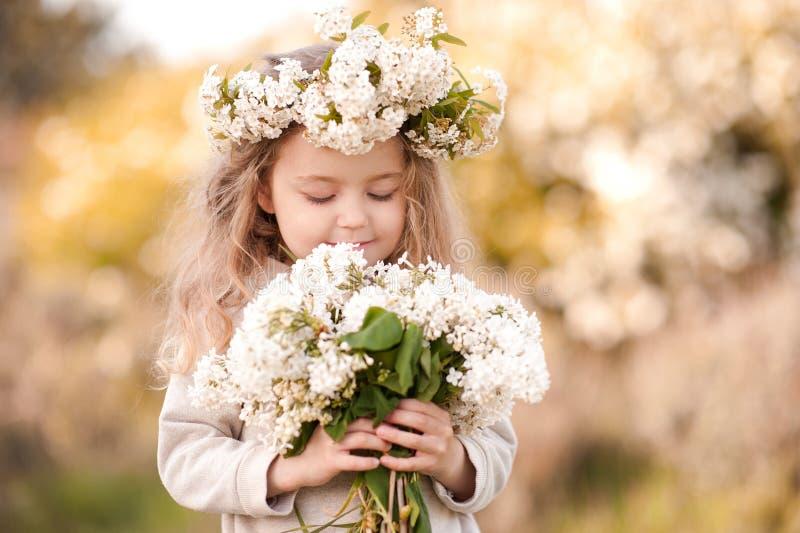 Bebé hermoso con las flores al aire libre fotografía de archivo
