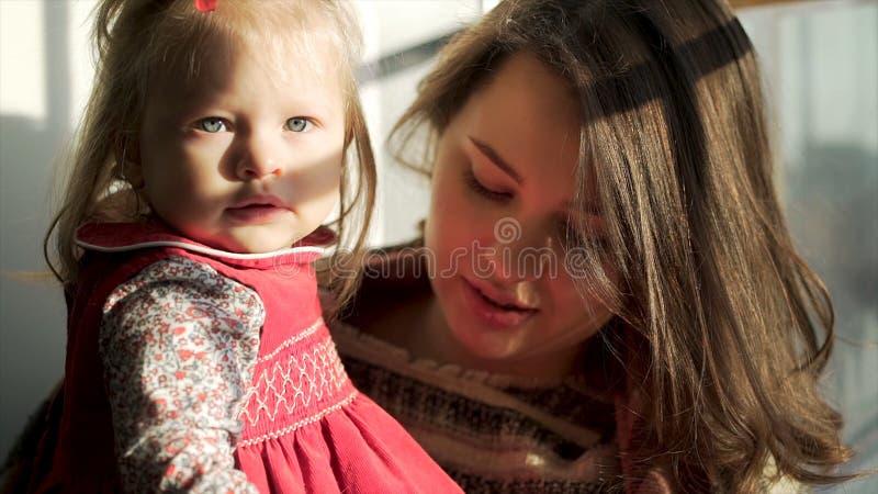 Bebé hermoso con las mejillas rechonchas lindas que miran derecho en sus brazos de la madre Niño precioso y su mamá contra fotografía de archivo libre de regalías