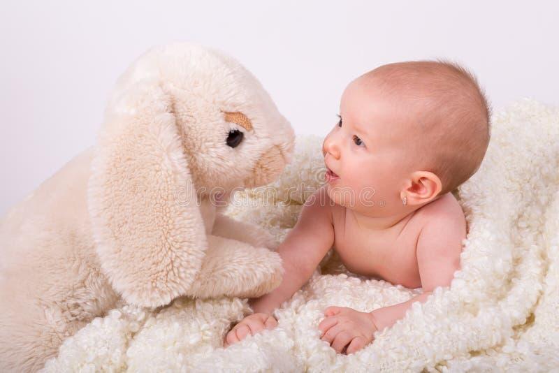 Bebé hermoso de la muchacha que juega con el conejito de pascua fotos de archivo