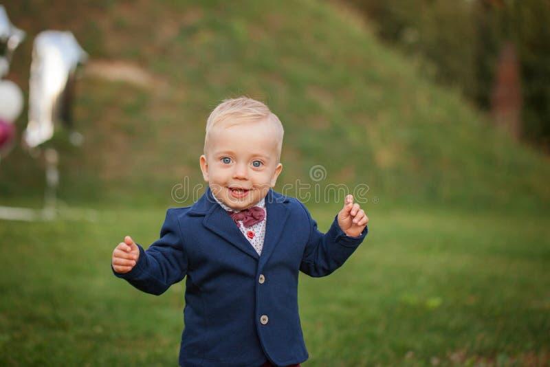 Bebé hermoso del retrato de la sonrisa Muchacho lindo de 1 año en la hierba Aniversario del cumpleaños imagenes de archivo