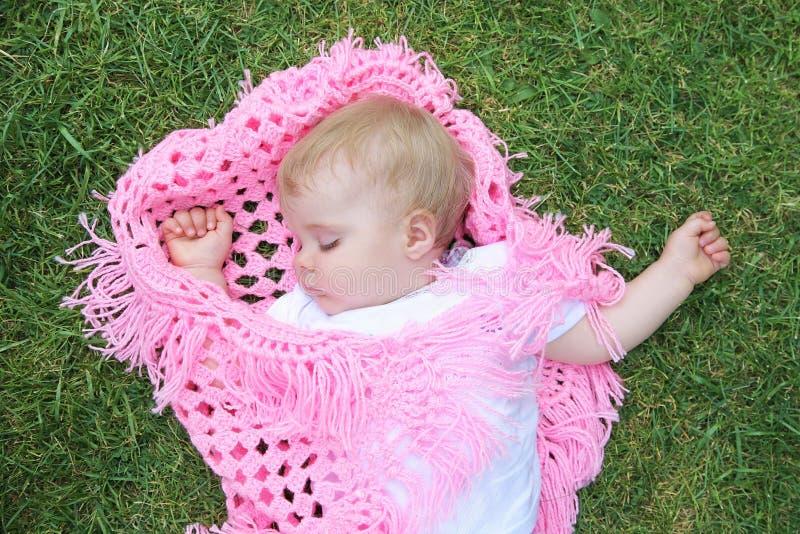 bebé hermoso dormido con la manta en gras verdes foto de archivo libre de regalías