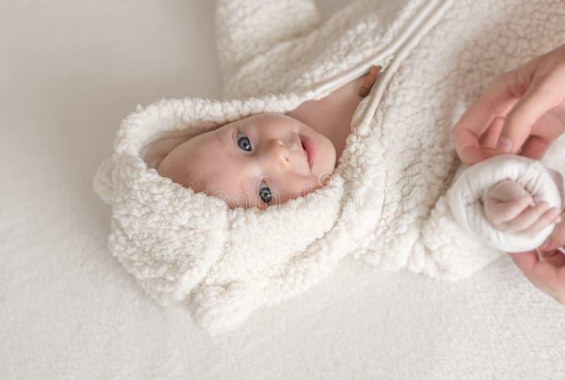 Bebé hermoso en un traje blanco caliente que miente en una cama foto de archivo libre de regalías