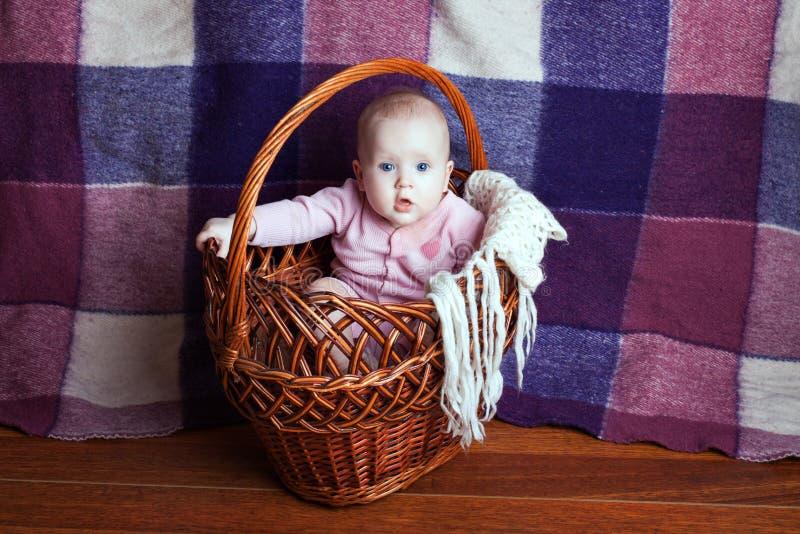 Bebé hermoso en una cesta imagenes de archivo