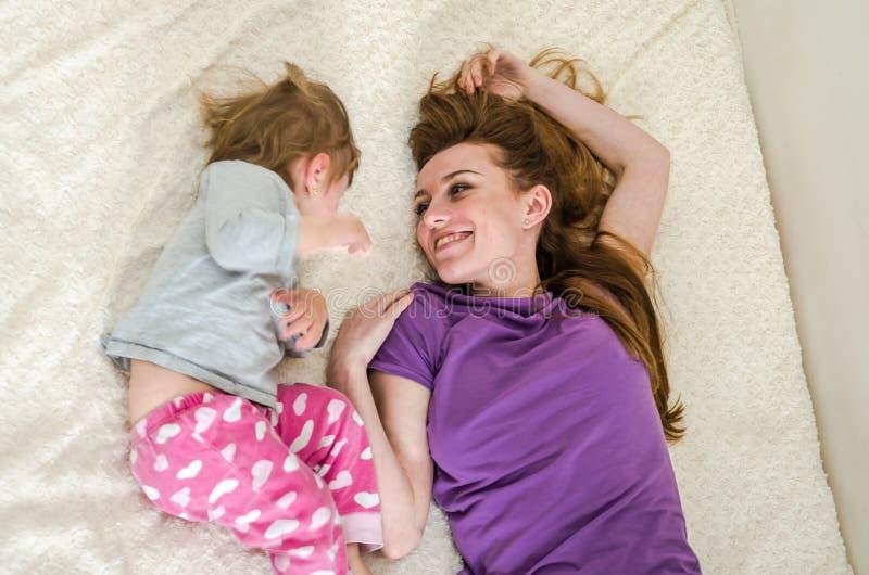 Bebé hermoso joven de la madre y de la hija que miente en la cama después de despertar por la mañana y el sorbo, familia feliz de fotos de archivo
