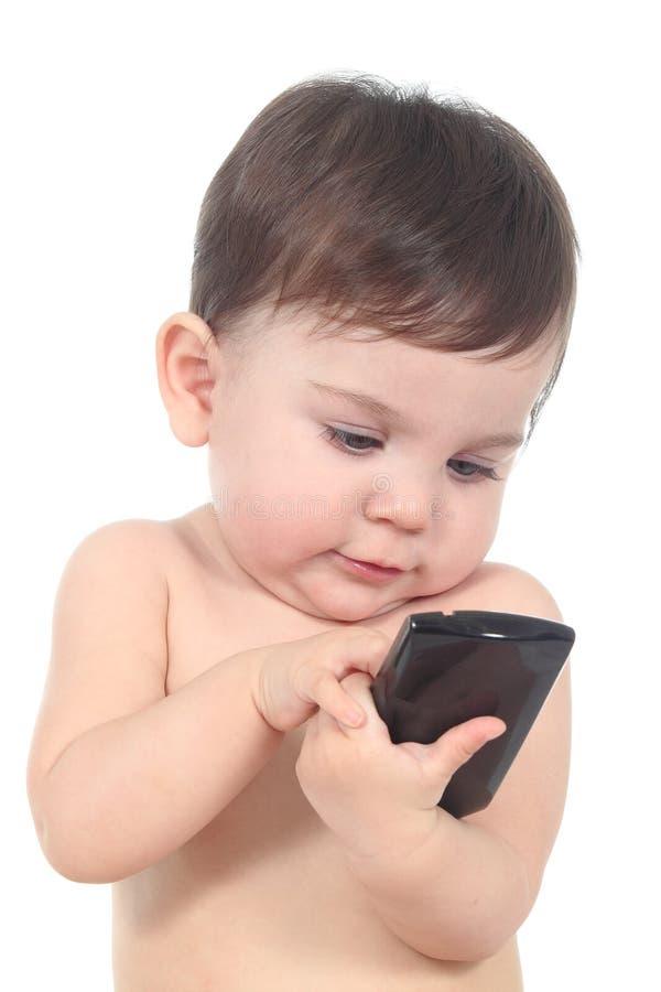 Bebé hermoso que juega y que toca un teléfono móvil imagenes de archivo