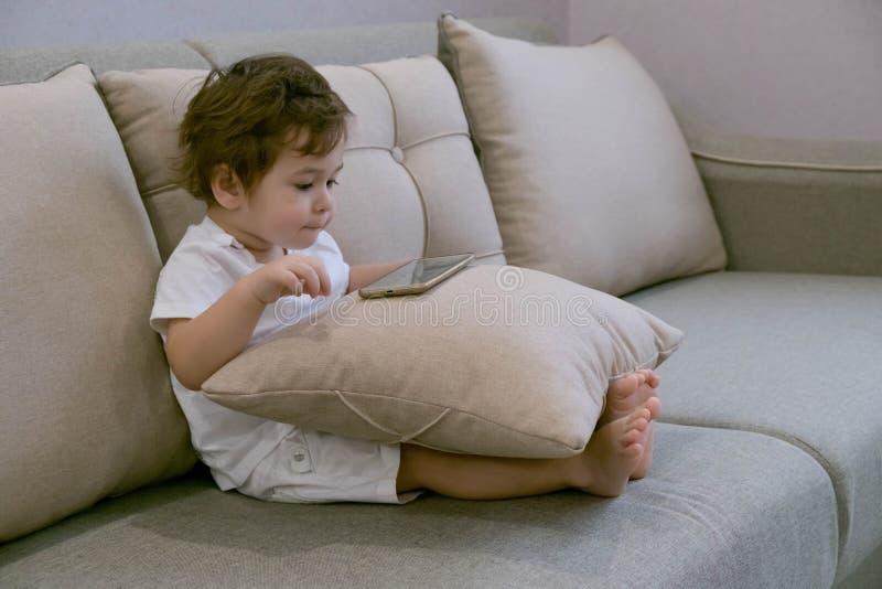 Bebé hermoso que juega y que toca un teléfono móvil Niño que aprende cómo utilizar smartphone Muchacho que manda un SMS en el tel imagenes de archivo