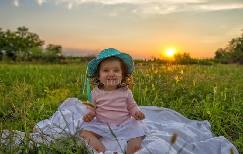 Bebé hermoso que se sienta en la manta en la puesta del sol foto de archivo