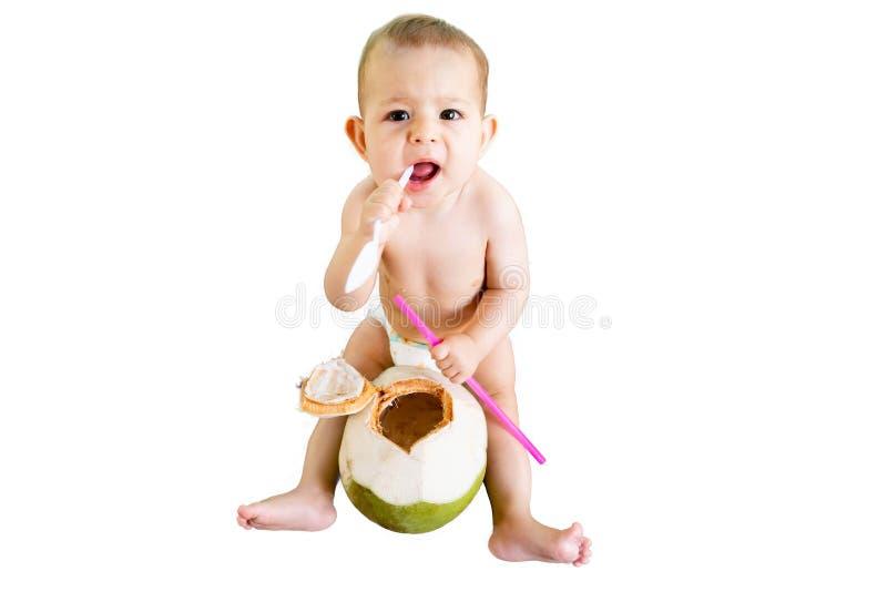 Bebé infantil feliz en las vacaciones tropicales Aislado come y bebe el coco joven verde Se sienta en una tabla de madera dentici fotografía de archivo