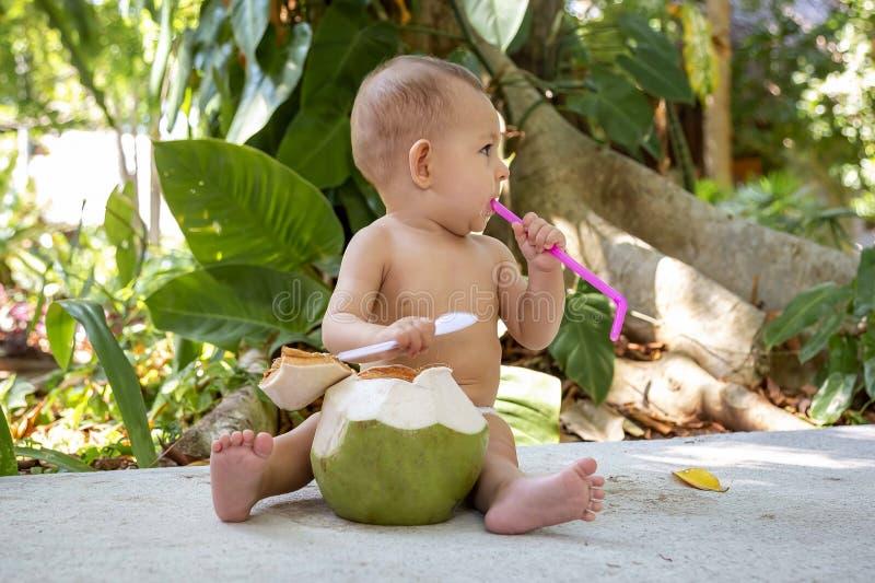 Bebé infantil feliz y alegre en las vacaciones tropicales Come y bebe el coco joven verde Se sienta en un piso y la mirada alrede foto de archivo