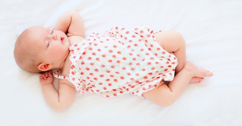Bebé infantil lindo en mono que duerme en cama Visión superior fotos de archivo libres de regalías