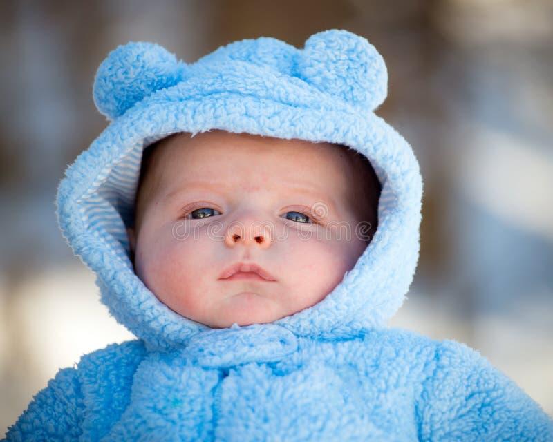 Bebé infantil lindo que lleva el traje mullido de la nieve imagenes de archivo