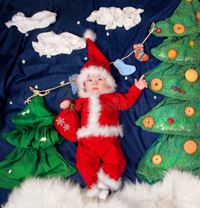 Bebé infantil que lleva el traje de Papá Noel que sostiene el bolso con los regalos fotografía de archivo libre de regalías