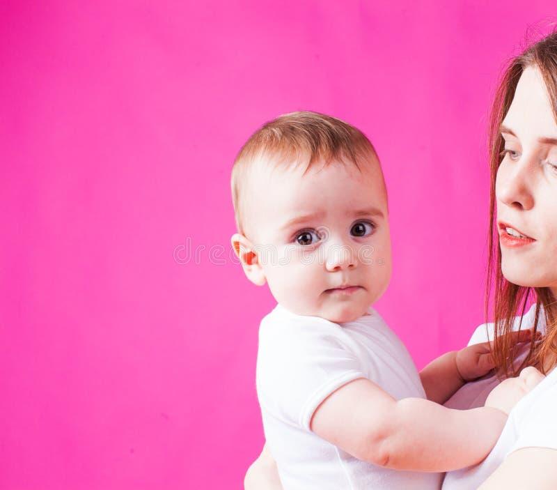 Bebé infantil que mira la cámara, fondo rosado imagenes de archivo