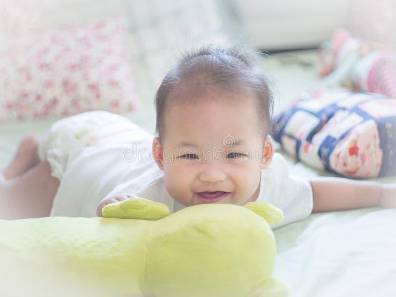Bebé infantil que se acuesta en la cama y la sonrisa imagen de archivo libre de regalías