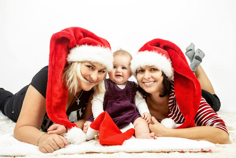 Bebé infantil sonriente con la mujer dos con los sombreros de santa foto de archivo