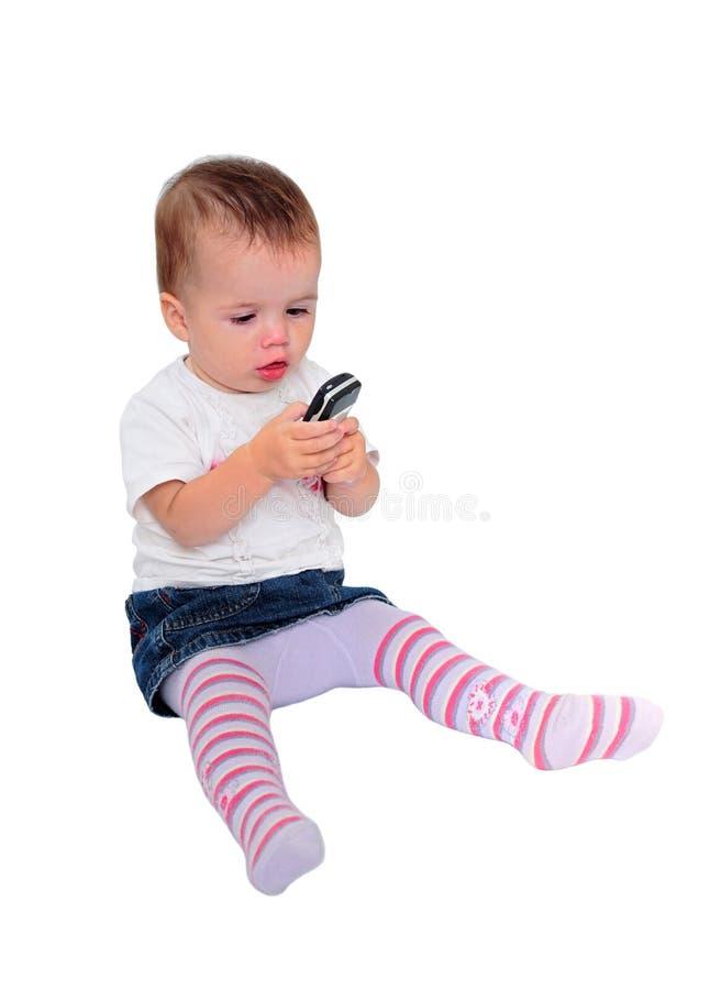 Bebé joven que envía mensajes de texto en el teléfono móvil imagen de archivo