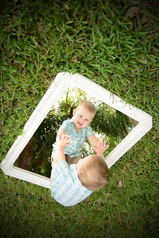 Bebé joven que mira a uno mismo en espejo fotografía de archivo