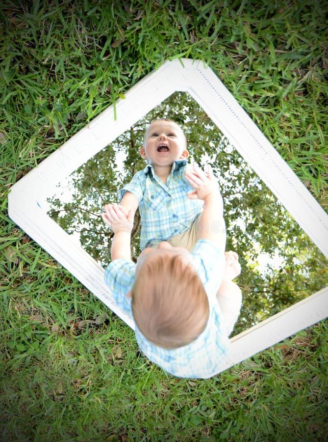 Bebé joven que mira a uno mismo en espejo mientras que sonríe imagen de archivo libre de regalías