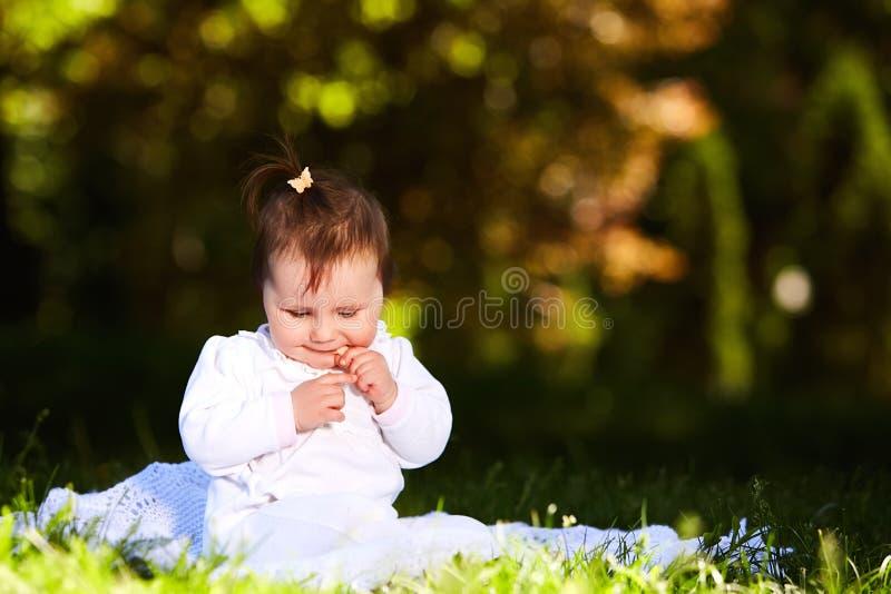 Bebé lindo adorable que se sienta en prado verde y que come los pasteles imagenes de archivo