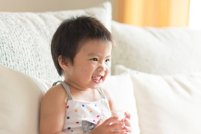 Bebé lindo asiático que sonríe y que sostiene un vidrio de agua Conce imagenes de archivo