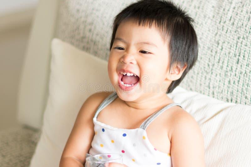 Bebé lindo asiático que sonríe y que sostiene un vidrio de agua Conce fotografía de archivo libre de regalías
