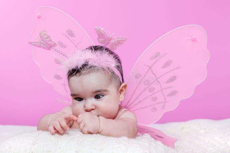 Bebé lindo, bonito, feliz, rechoncho curioso sobre sus manos que cruzan ojos para enfocarse imagen de archivo