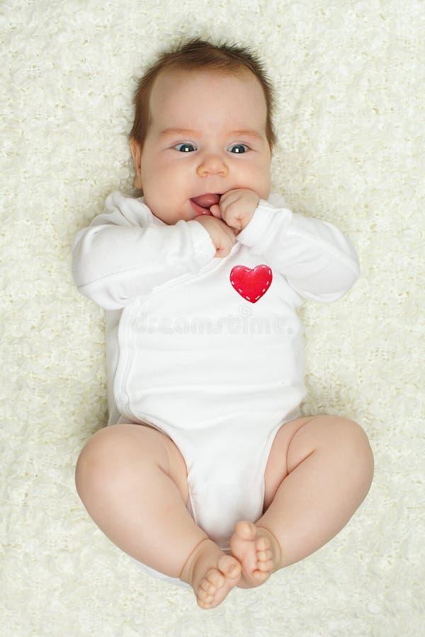 Bebé lindo con el corazón rojo fotos de archivo