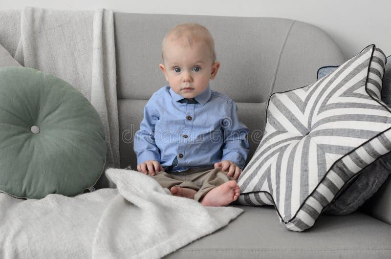 Bebé lindo con el pelo rubio y los ojos azules que se sientan en el sofá y foto de archivo libre de regalías