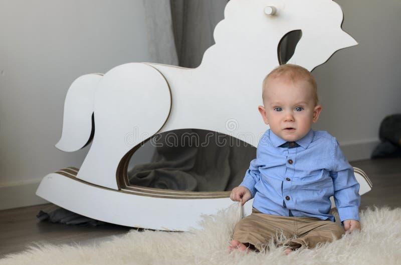 Bebé lindo con el pelo rubio y los ojos azules que sientan y que miran c imagen de archivo