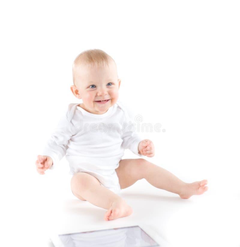 Bebé lindo con la tablilla digital fotografía de archivo