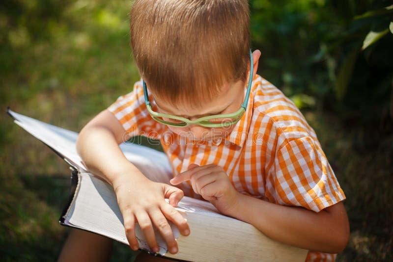 Bebé lindo con los vidrios que lee el libro en día de verano Al aire libre, de nuevo a concepto de la escuela foto de archivo