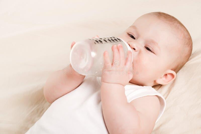 Bebé lindo con una botella de leche en una manta beige fotos de archivo