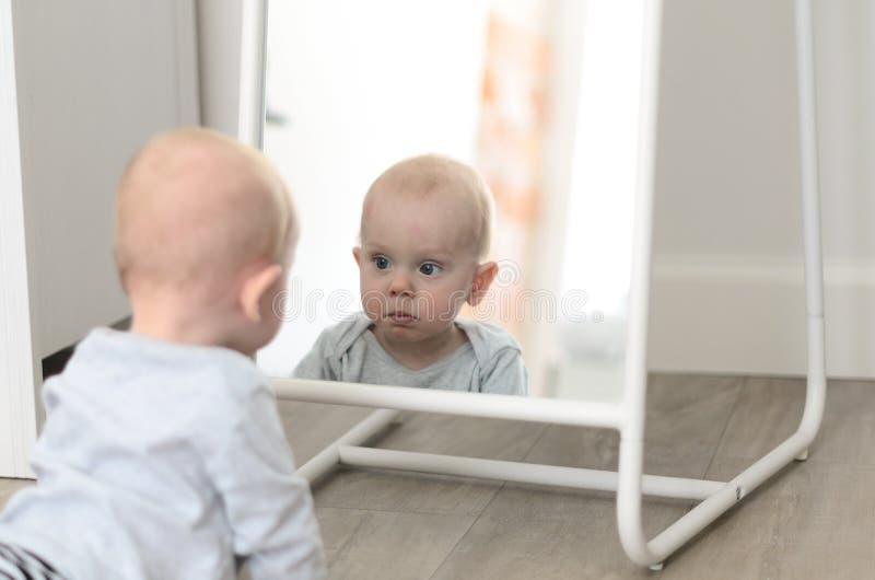 Bebé lindo de la diversión que ve a uno mismo en espejo imagen de archivo