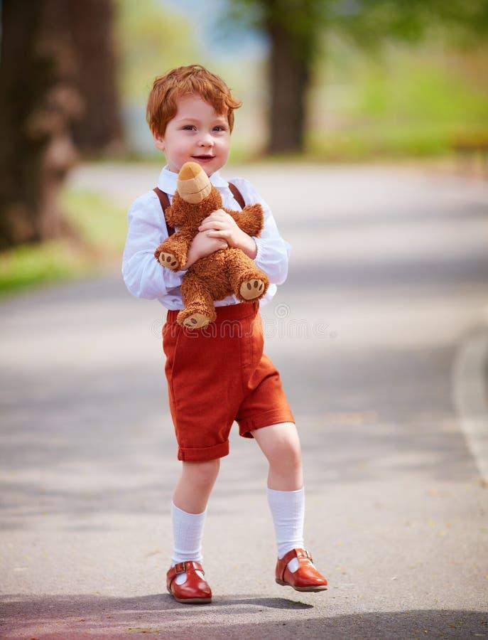 Bebé lindo del pelirrojo con el oso de la felpa que camina en parque de la primavera fotos de archivo libres de regalías