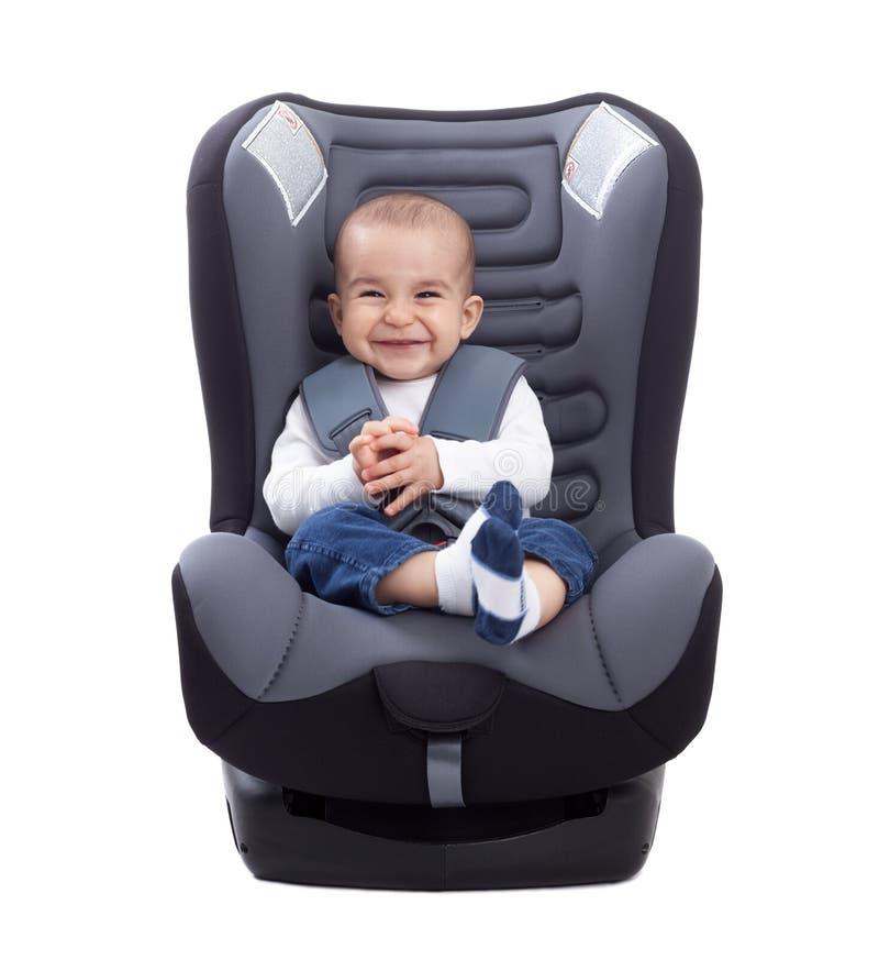 Bebé lindo divertido que se sienta en un asiento de carro, aislado foto de archivo